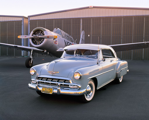 AUT 21 RK1670 02 © Kimball Stock 1952 Chevy Bel Air Hardtop Beige 3/4 Front View On Pavement By Airplane