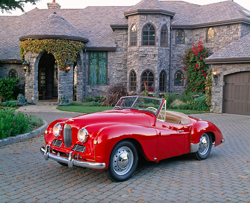 AUT 21 RK1676 02 © Kimball Stock 1951 Jowett Jupiter Roadster Red 3/4 Front View On Driveway By House