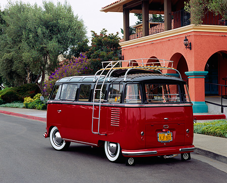 AUT 21 RK1818 02 © Kimball Stock 1956 VW Deluxe Bus Red And Brown 3/4 Rear View On Pavement By Building And Trees