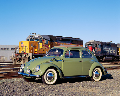 AUT 21 RK1819 02 © Kimball Stock 1952 VW Sunroof Beetle Green 3/4 Side View On Gravel By Train