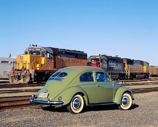 AUT 21 RK1821 03 © Kimball Stock 1952 VW Sunroof Beetle Green 3/4 Rear View On Gravel By Train