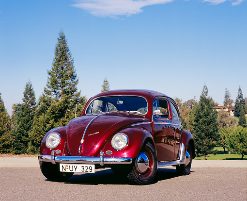 AUT 21 RK1838 01 © Kimball Stock 1956 Volkswagen Oval Bug Red 3/4 Front View On Pavement Trees Background