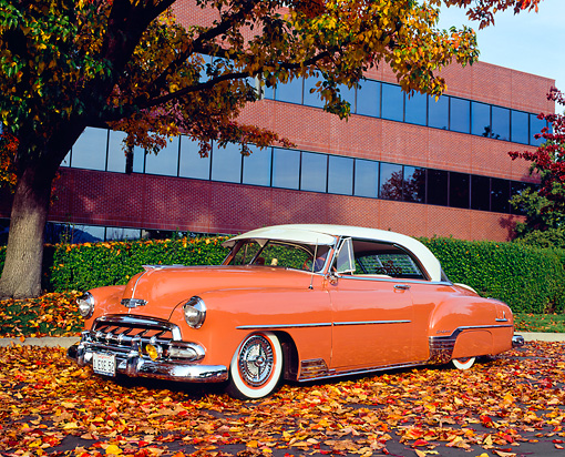 AUT 21 RK1853 02 © Kimball Stock 1952 Chevy Deluxe Salmon And White 3/4 Front View On Fall Leaves By Building