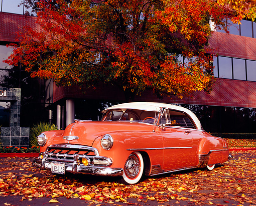 AUT 21 RK1854 01 © Kimball Stock 1952 Chevrolet Deluxe Salmon And White Low 3/4 Front View By Autumn Tree And Building