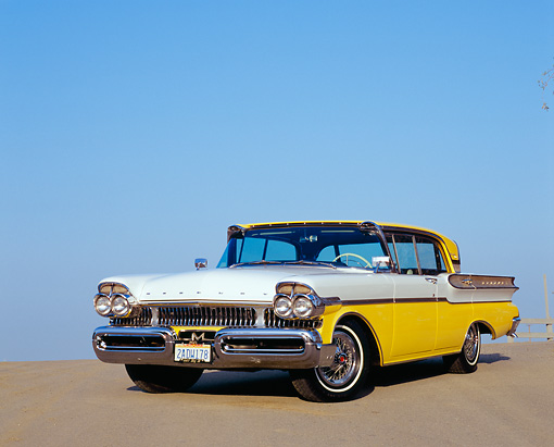 AUT 21 RK1861 03 © Kimball Stock 1957 Mercury Turnpike Cruiser Yellow And White Low 3/4 Front View On Pavement Blue Sky