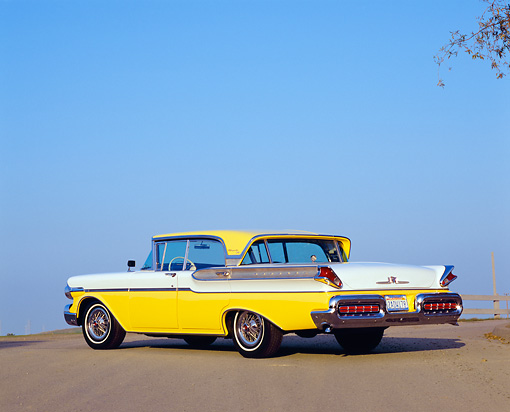 AUT 21 RK1865 02 © Kimball Stock 1957 Mercury Turnpike Cruiser Yellow And White Low 3/4 Rear View On Pavement Blue Sky