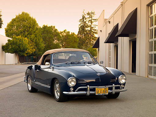 AUT 21 RK2032 01 © Kimball Stock 1959 Volkswagen Karmann Ghia 141 Convertible Blue 3/4 Front View On Pavement By Building
