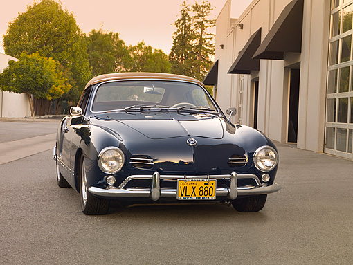 AUT 21 RK2033 01 © Kimball Stock 1959 Volkswagen Karmann Ghia 141 Convertible Blue 3/4 Front View On Pavement By Building