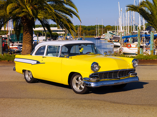 AUT 21 RK2097 01 © Kimball Stock 1956 Ford Mainline Yellow And White 3/4 Front View On Pavement By Harbor