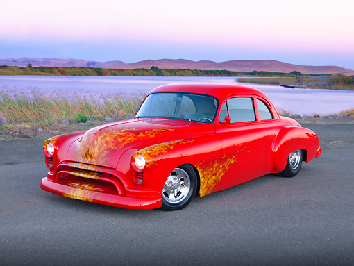 AUT 21 RK2272 01 © Kimball Stock 1950 Oldsmobile 88 Hot Rod Red With Flames Custom Coupe 3/4 Front View On Pavement By Water