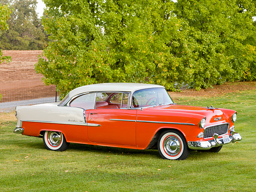 AUT 21 RK2297 01 © Kimball Stock 1955 Chevrolet Bel Air Hardtop Red And Beige 3/4 Front View On Grass By Trees