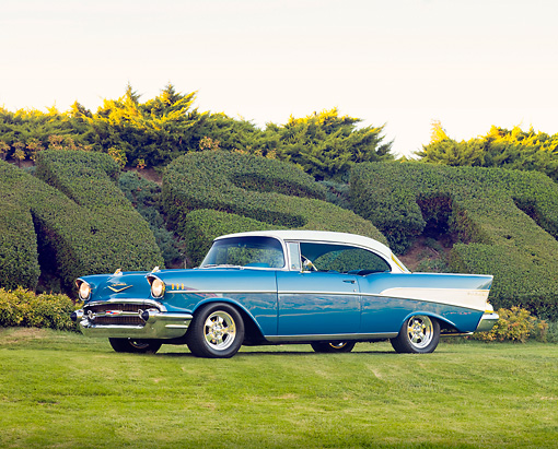 AUT 21 RK2301 01 © Kimball Stock 1957 Chevrolet Bel Air Hardtop Blue And White 3/4 Front View On Grass By Hedge