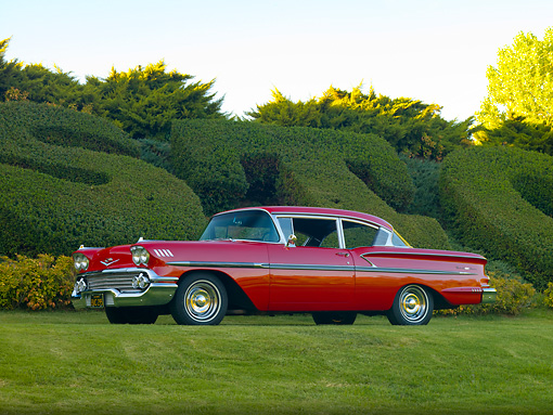 AUT 21 RK2302 01 © Kimball Stock 1958 Chevrolet Bel Air Hardtop Red 3/4 Front View On Grass By Hedge