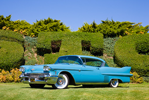 AUT 21 RK2317 01 © Kimball Stock 1958 Cadillac Series 62 Coupe Blue 3/4 Front View On Grass By Hedge