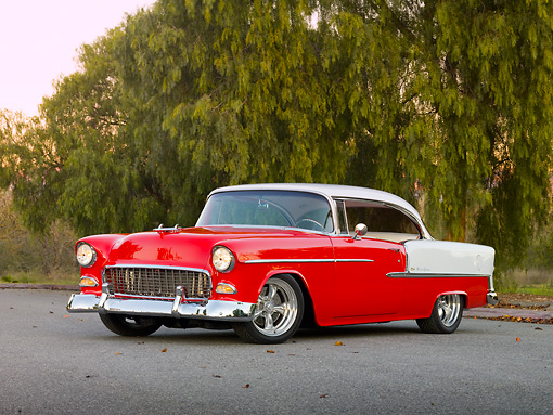 AUT 21 RK2335 01 © Kimball Stock 1955 Chevrolet Bel Air Red And White 3/4 Front View On Pavement By Trees