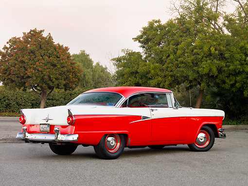 AUT 21 RK2337 01 © Kimball Stock 1956 Ford Customline Victoria Red And White 3/4 Rear View On Pavement By Trees
