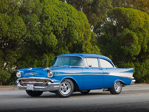 AUT 21 RK2365 01 © Kimball Stock 1957 Chevrolet Bel Air 210 Blue 3/4 Front View On Pavement By Trees