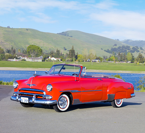 AUT 21 RK2379 01 © Kimball Stock 1951 Chevrolet Bel Air Convertible Red 3/4 Front View On Pavement By Lake