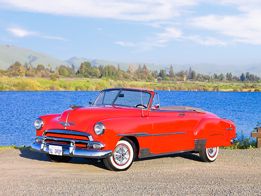 AUT 21 RK2380 01 © Kimball Stock 1951 Chevrolet Bel Air Convertible Red 3/4 Front View On Pavement By Lake