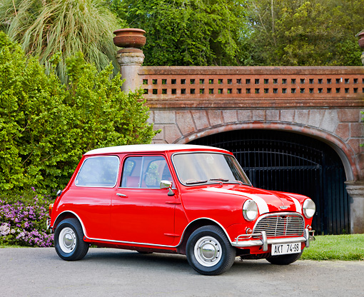 AUT 22 BK0024 01 © Kimball Stock 1961 Mini Mark I Red With White Stripes 3/4 Front View On Pavement By Bridge