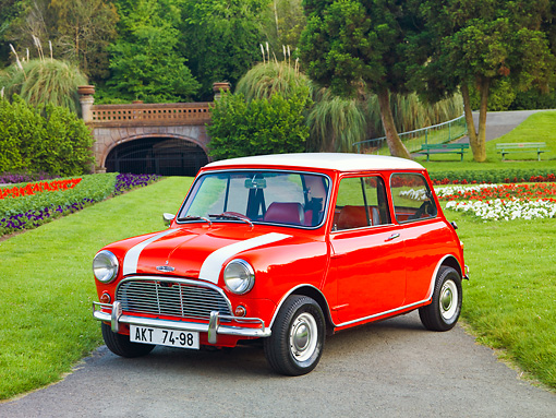 AUT 22 BK0026 01 © Kimball Stock 1961 Mini Mark I Red With White Stripes 3/4 Front View On Pavement By Garden