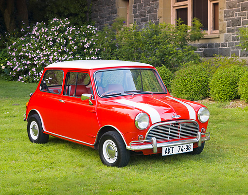 AUT 22 BK0028 01 © Kimball Stock 1961 Mini Mark I Red With White Stripes 3/4 Front View On Grass By Building
