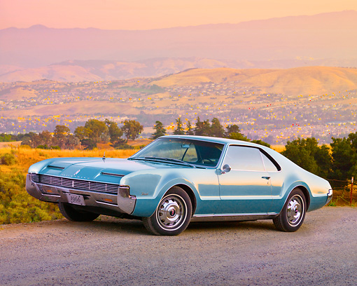 AUT 22 BK0047 01 © Kimball Stock 1966 Oldsmobile Toronado Blue 3/4 Front View On Gravel By Hills
