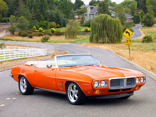 AUT 22 BK0051 01 © Kimball Stock 1969 Pontiac Firebird Convertible Orange 3/4 Front View On Road By House On Hill