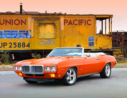 AUT 22 BK0053 01 © Kimball Stock 1969 Pontiac Firebird Convertible Orange 3/4 Front View On Pavement By Train