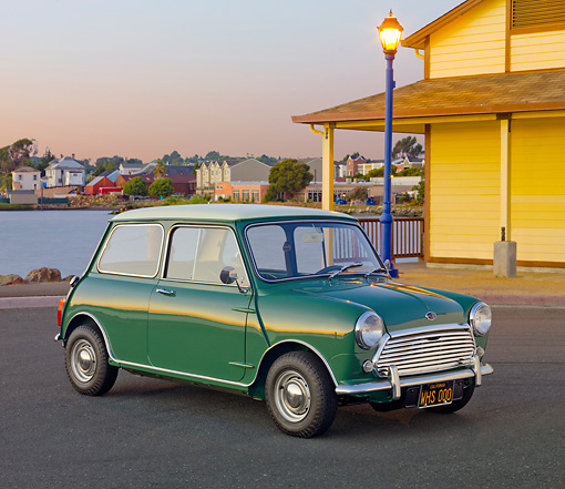 AUT 22 BK0086 01 © Kimball Stock 1967 Austin Mini Cooper Mark II Green 3/4 Front View On Pavement By Water And Houses At Dusk