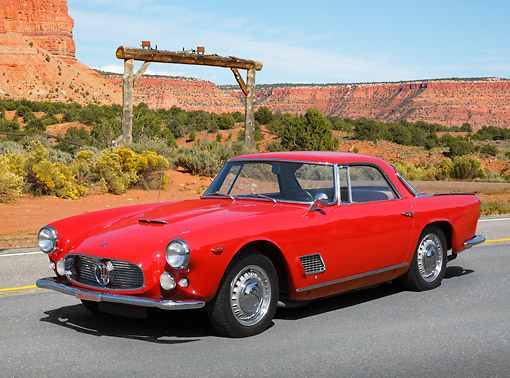 AUT 22 BK0113 01 © Kimball Stock 1960 Maserati 3500 GT Red 3/4 Front View On Road In Desert