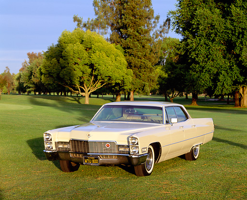 AUT 22 RK0193 06 © Kimball Stock 1968 Cadillac Sedan De Ville Yellow 3/4 Front View On Grass By Trees