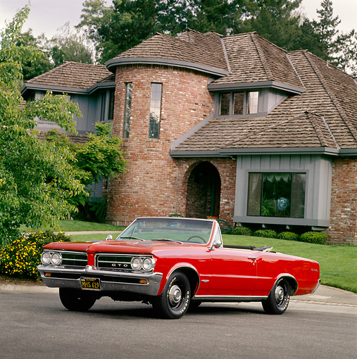 AUT 22 RK0267 03 © Kimball Stock 1964 Pontiac GTO Convertible Red 3/4 Front View Shot On Driveway In Front Of House