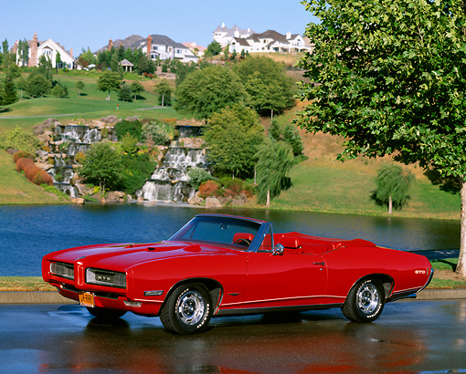 AUT 22 RK0319 16 © Kimball Stock 1968 Pontiac GTO Convertible Red 3/4 Side View On Wet Pavement By Water And Grass Hills