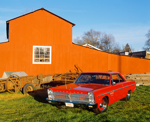 AUT 22 RK0989 04 © Kimball Stock 1965 Plymouth Sport Fury Red 3/4 Front View On Grass By Barn Blue Sky