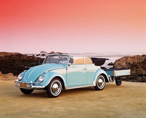 AUT 22 RK1154 04 © Kimball Stock 1962 VW Karmann Convertible Blue With Trailer 3/4 Front View On Sand By Rocks And Water Pink Sky