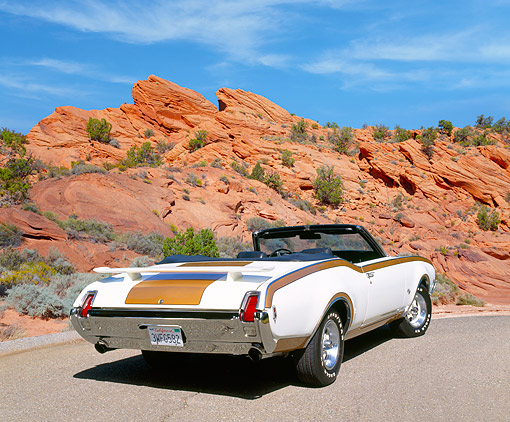 AUT 22 RK1492 02 © Kimball Stock 1969 Oldsmobile 455 Hurst Convertible White And Gold Rear 3/4 View On Pavement In Desert
