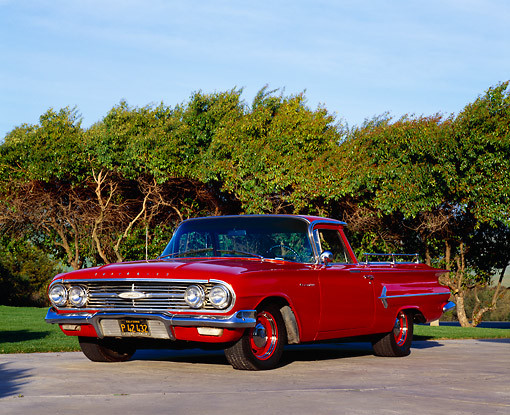 AUT 22 RK1674 03 © Kimball Stock 1960 Chevy El Camino Red Low 3/4 Front View On Pavement Trees Background Blue Sky