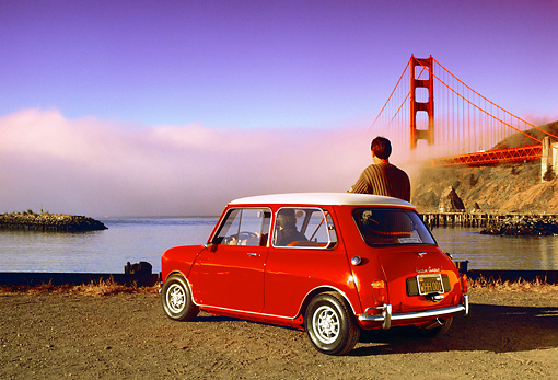 AUT 22 RK1744 06 © Kimball Stock 1967 Austin Mini Cooper S Red And White 3/4 Rear View By Golden Gate Bridge With Man