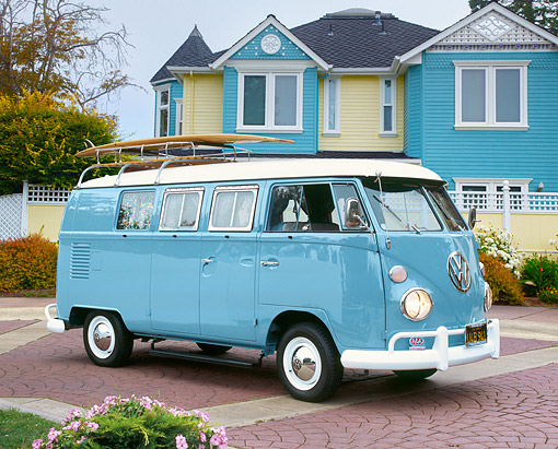 AUT 22 RK1789 01 © Kimball Stock 1967 VW Bus Blue And White With Surfboard 3/4 Front View On Brick By House