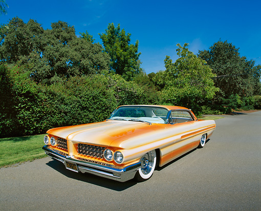 AUT 22 RK1802 02 © Kimball Stock 1962 Pontiac Grand Prix Custom Orange 3/4 Front View On Pavement By Trees