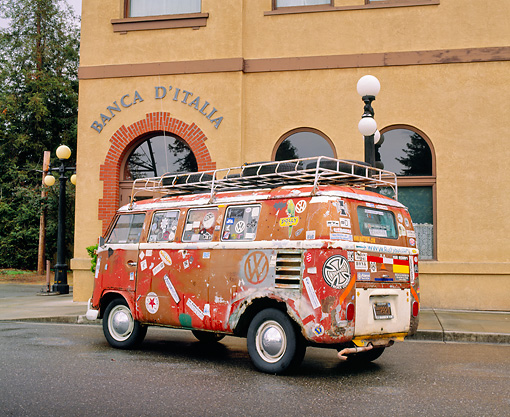 AUT 22 RK1924 01 © Kimball Stock 1961 VW Bus Ragtop Rusty With Stickers 3/4 Rear View On Pavement By Building