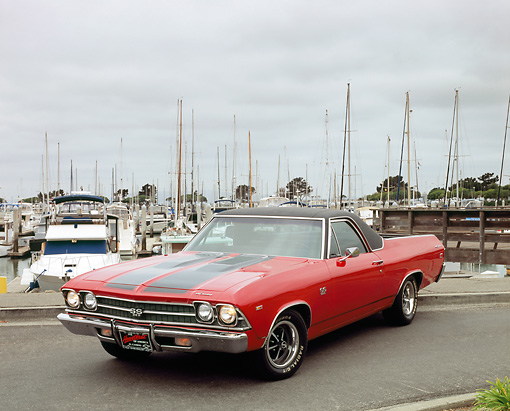 AUT 22 RK2079 01 © Kimball Stock 1969 Chevy El Camino Red Black Stripe 3/4 Front View On Pavement By Harbor