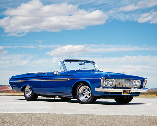 AUT 22 RK2163 01 © Kimball Stock 1963 Plymouth Fury Convertible Blue Low 3/4 Side View On Pavement Blue Sky