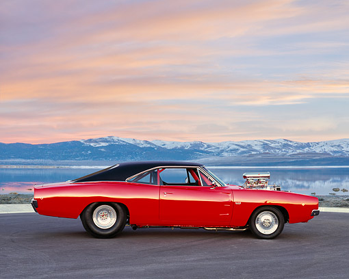 AUT 22 RK2299 01 © Kimball Stock 1968 Dodge Charger R/T 528  Hemi Orange Low Profile On Pavement By Lake And Snowy Mountains