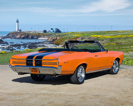 AUT 22 RK2438 01 © Kimball Stock 1966 Pontiac GTO Convertible Orange Black Stripes 3/4 Rear View On Sand By Lighthouse