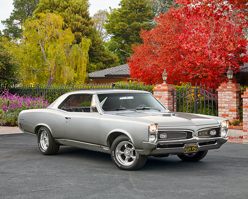 AUT 22 RK2508 01 © Kimball Stock 1967 Pontiac GTO Silver 3/4 Front View On Pavement By Gate And Autumn Trees