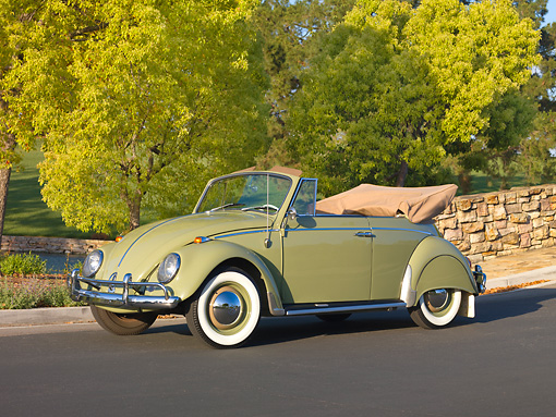 AUT 22 RK2808 01 © Kimball Stock 1965 Volkswagen Beetle Cabriolet Green 3/4 Front View On Pavement By Stone Wall And Trees