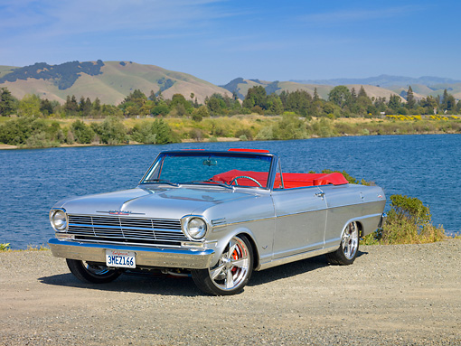 AUT 22 RK2820 01 © Kimball Stock 1962 Chevrolet Nova 400 Convertible Silver 3/4 Front View On Gravel By Lake And Hills