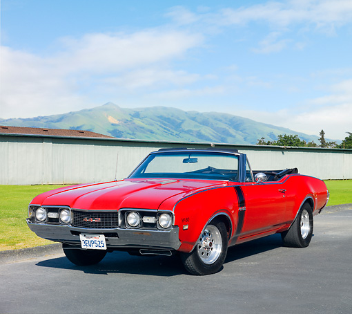AUT 22 RK2856 01 © Kimball Stock 1968 Oldsmobile 442 W-30 Convertible Red 3/4 Front View On Pavement By Grass And Mountains